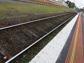 photo of train tracks parallel to station and platform edge markers. poster