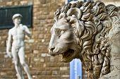 Statue of a lion at the Loggia dei Lanzi in Piazza della Signoria and copy Michelangelo's sculpture of David front of the Palazzo Vecchio at background in Florence, Italy poster