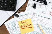 Paper sheet with text TAX DEADLINE and individual tax return form on table poster