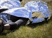 People wrapped in foil to keep warm laying on grass at the finish line after an endurance race. poster