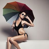Beautiful woman in stylish black swimwear and sunglasses holding colorful umbrella. Perfect slim tanned body. poster