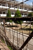 Shot of the main block of the notorious S21 prison in Phnom Phen with razor wire in the foreground and the courtyard and prison block in the middle and background poster