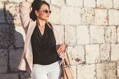 Young stylish woman wearing neutral blazer, sunglasses and handbag walking on the city street in spring. Casual fashion, elegant look. Plus size model. poster