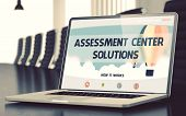 Assessment Center Solutions on Landing Page of Laptop Screen. Closeup View. Modern Meeting Room Background. Blurred Image with Selective focus. 3D. poster