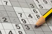 Closeup of an incomplete Sudoku puzzle with a pencil poster