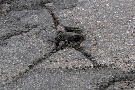 A pot hole in the asphalt road with cracks in need of maintenance