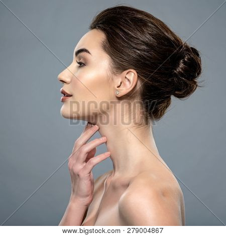 Beautiful woman cares for the skin neck- posing at studio isolated on white. Beautiful face of  a caucasian model with clean fresh skin.