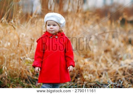 Outdoor Portrait Of Little Cute Toddler Girl In Red Coat And White Fashion Hat Barret. Healthy Happy