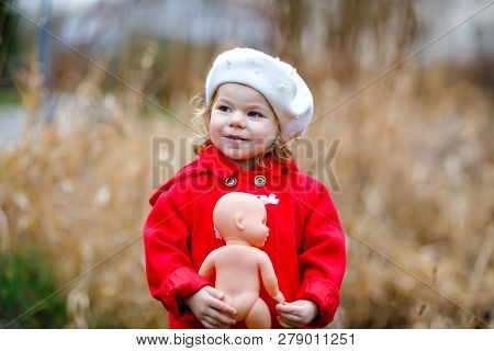 Outdoor Portrait Of Little Cute Toddler Girl In Red Coat And White Fashion Hat Barret With Toy Doll.