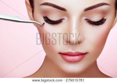poster of Beautiful Woman with Extreme Long False Eyelashes. Eyelash Extensions. Makeup, Cosmetics. Beauty, Skincare. Woman Glues Eyelashes