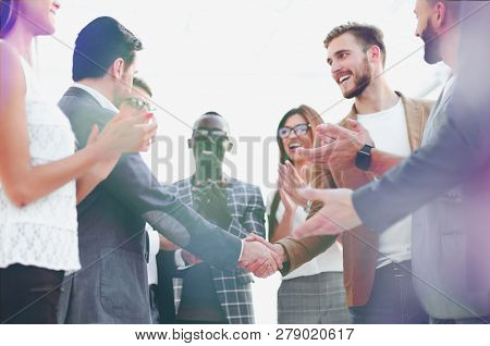 handshake of business partners and applauding business team