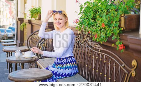 Woman winking face have drink cafe terrace outdoors. Girl drink tea with milk as aristocratic tradition. Mug of good tea with milk in morning gives me energy charge. Traditional tea with milk poster