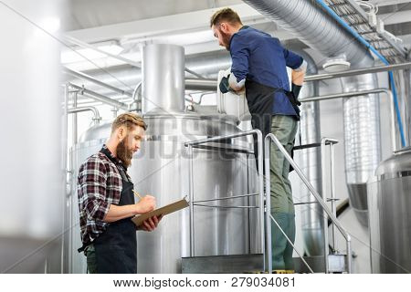 manufacture, business and people concept - men with clipboard and malt working at brewery or beer plant kettle poster