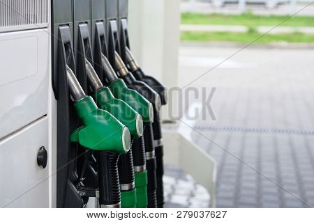 Green And Black Fuel Pistols On Fuel Station. Gas Station And Petroling Concept. Pumping Gas At Gas