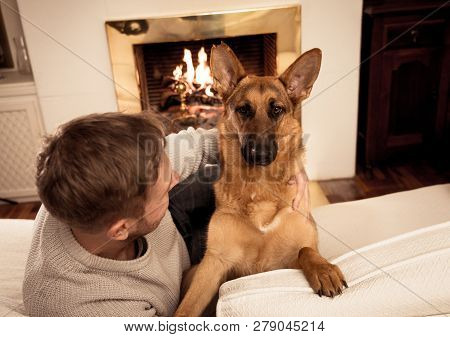 Cute Portrait Of Young Man And Dog German Shepherd Hugging At Cozy Home In Winter