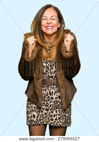 Beautiful middle age elegant woman wearing mink coat excited for success with arms raised celebrating victory smiling. Winner concept.