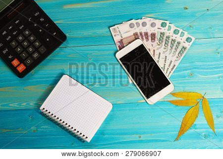 Autumn Leaf, Broken Smartphone And Money On A Blue Wooden Table. Unforeseen Expenses Have Disrupted