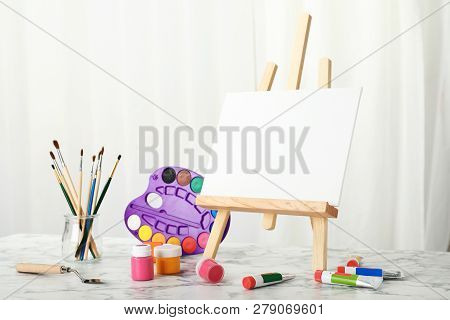 Wooden Easel With Blank Canvas Board And Painting Tools For Children On Table In Room