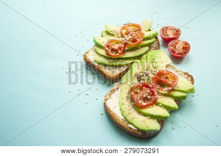 Flat Lay Of Delicious Toasts With Sliced Avocado, Tomatoes And Sesamum Seeds On Blue Background With