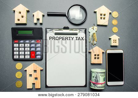 Table With Wooden Houses, Calculator, Coins, Magnifying Glass With The Word Property Tax. Property T