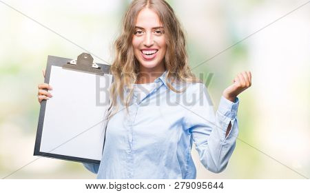 Beautiful young blonde business woman holding clipboard over isolated background screaming proud and celebrating victory and success very excited, cheering emotion