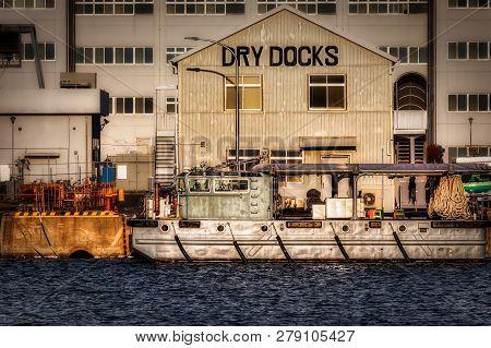 A Small Boat Sits Moored At A Dock In Yokosuka, Japan.