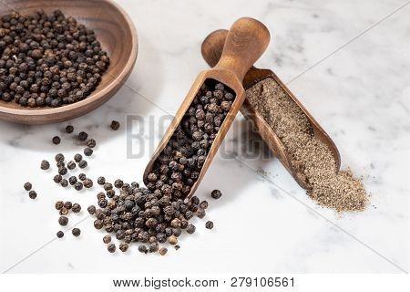 Black Pepper Seeds And Black Pepper Ground On Marble Background. Spices For Cooking. Piper Nigrum