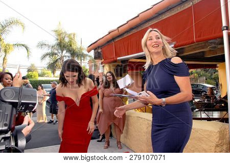 Olivia Applegate (red dress) attends  the