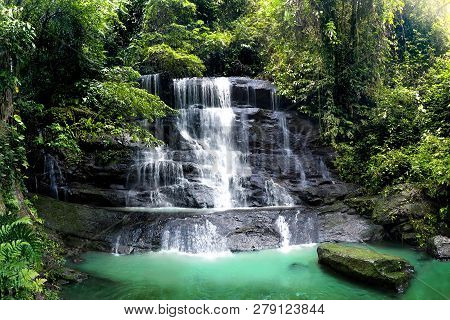 Waterfall Cascade In Tropical Rainforest With Big Rock Cover With Green Moss After Rain. Taken In Ca