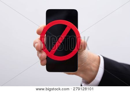Business Person Showing Red No Sign On Mobile Phone
