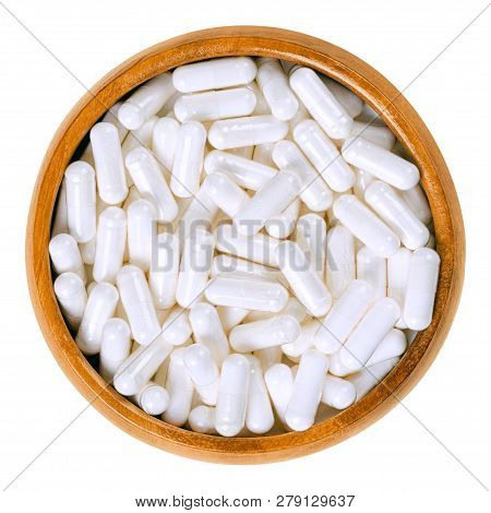 White Food Supplement Capsules In Wooden Bowl. Hard Shelled Capsules, Filled With Powder, For Exampl