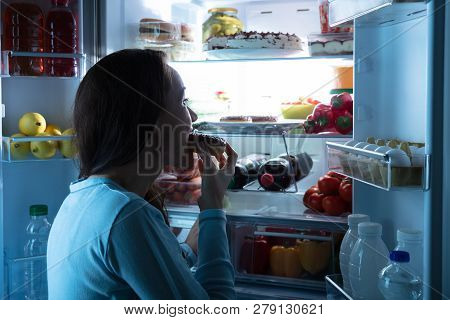 Side View Of A Young Woman Standing In Front Of Refrigerator Eating Donut