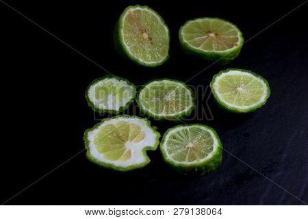 Bergamot Or Kaffir Lime Cut Half Isolate On Black Background