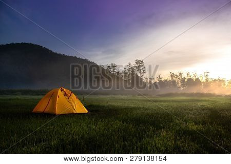 Yellow Camping Tent In The Middle Of Open Field Near Forest During Sunrise At Misty Morning. Concept
