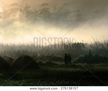 Silhouette Of Couple Standing Outside The Tent On Camping Ground Waiting For Sunrise At Foggy Mornin