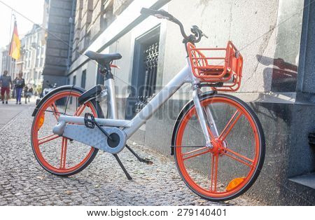 Healthy lifestyle concept. Bicycle with grey and orange color is parked near a wall. Blur buildings background. Close up view.
