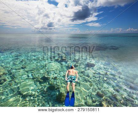 Snorkeling man on the Maldives beach
