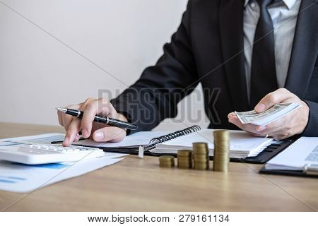 Businessman Accountant Counting Money And Making Notes At Report Doing Finances And Calculate About