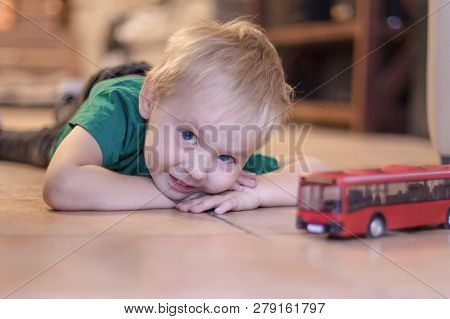 Adorable Little Boy With Blue Eyes And Crafty Smile Lays On The Ceramic Floor With Toy (red Bus). Bl