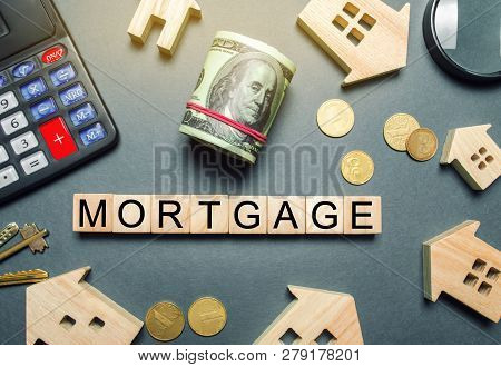 Wooden Houses, A Calculator, Keys, Coins And Blocks With The Word Mortgage. Buying A Home In Debt. P
