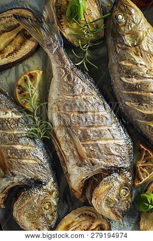 Grilled Gilt-head bream fish with vegetables and spices poster
