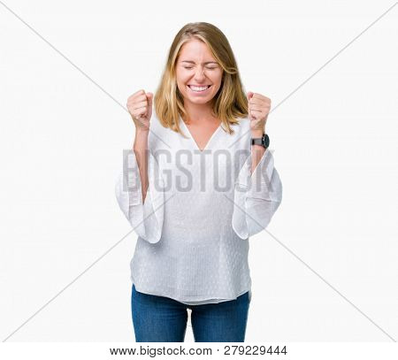 Beautiful young elegant woman over isolated background excited for success with arms raised celebrating victory smiling. Winner concept.