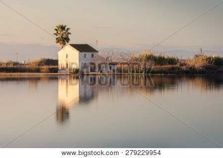 Beautiful Landscape With Farmhouse In Albufera Lagoon, Reflection, Blue Sky And Yellow Sunlight In S