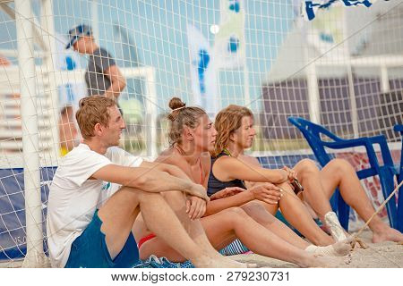 Beach Volleyball. Game Ball Under Sunlight And Blue Sky. A Group Of Volleyball Players Waiting To Pl