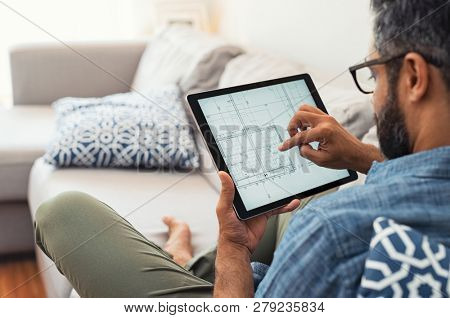 Man hand working with tablet and blueprint on architectural project at home while relaxing on couch. Back view of latin architect reading plan layout on digital tablet.