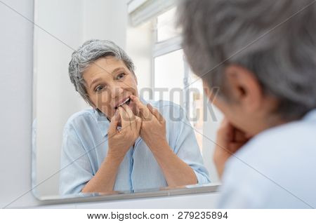Mature beautiful woman cleaning her teeth with floss in bathroom. Reflection of senior woman in bathroom mirror while cleaning teeth with dental floss. Healthcare and oral hygiene concept.