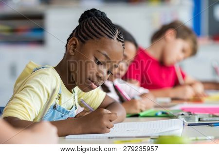 Cute pupil writing at desk in classroom at the elementary school. Student girl doing test in primary school. Children writing notes in classroom. African schoolgirl writing during the lesson.