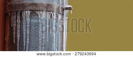 Icicles Hanging From Iron Pipe. Frozen Water And Metal Surface, Winter Time Concept. Selective Focus