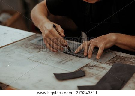 Handmade leather artisan making craft wallet using piece of natural leather on his working place with tools, close up photo of his hands poster