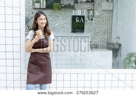 Portrait Of A Happy Young Asian Barista In Apron Holding Hot Coffee And Standing In Front Of Her Sma